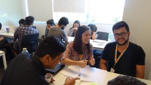Grupo de trabalho rindo à frente, com outros dois grupos no fundo